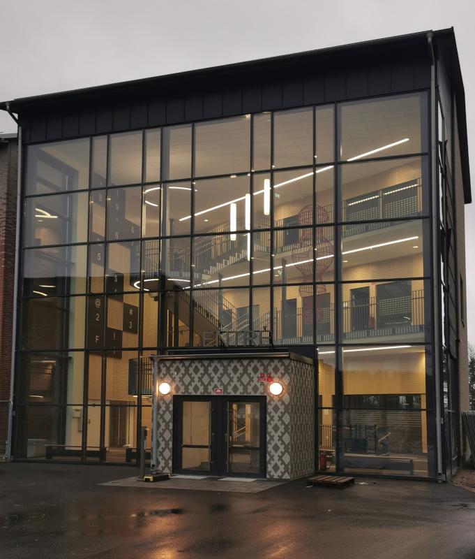 Glasentre med betongfasad i Krabbasnårmönster av mfj-form, närbild.